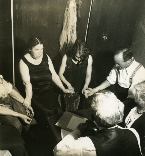 Guests hold hands in T.G. Hamilton's seance room.