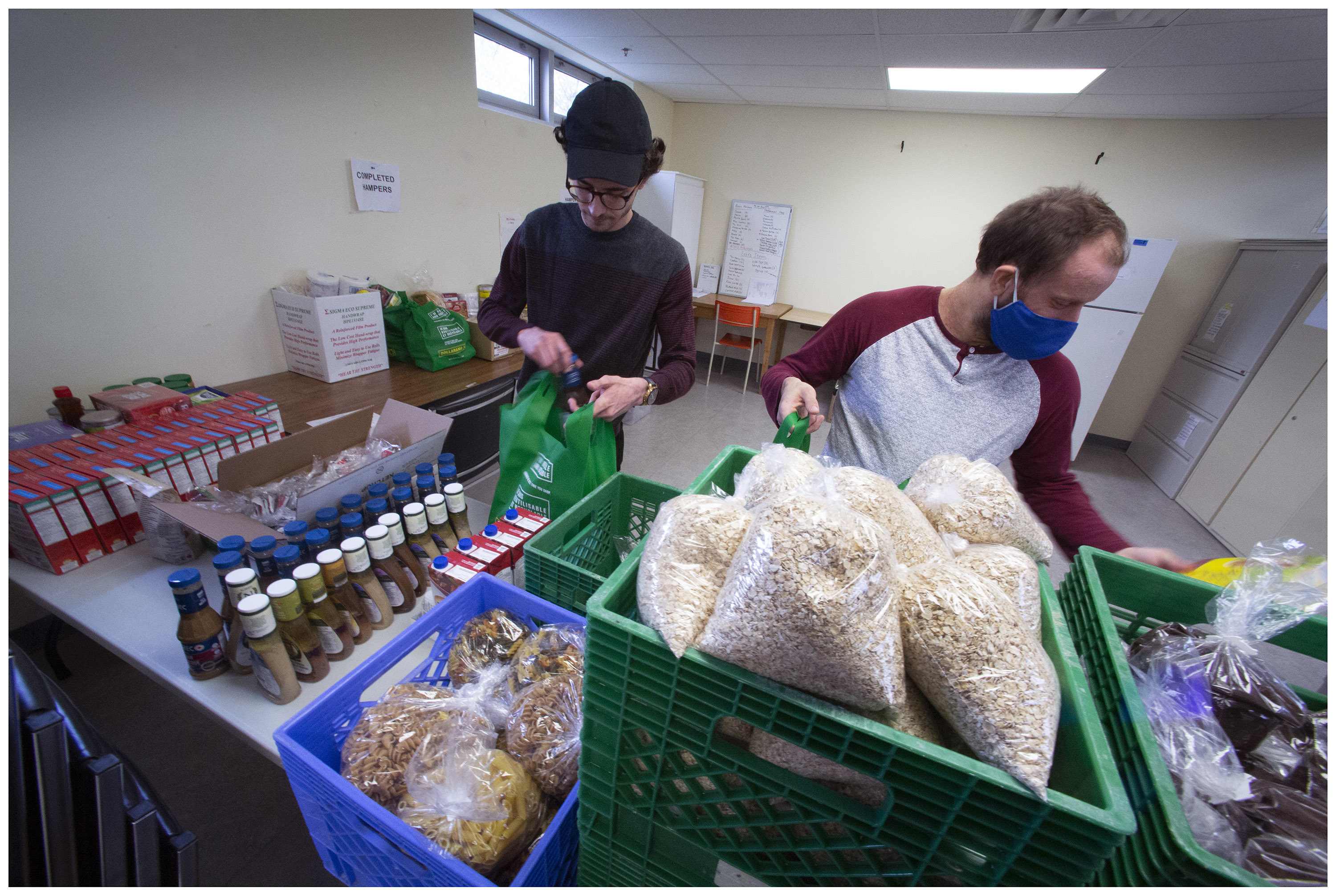 Jared Davis and Nick Baxter prepare food hampers at The Gathering Place. The non-profit organization changed its tactics when the lockdown started. (Photo by Paul Daly)