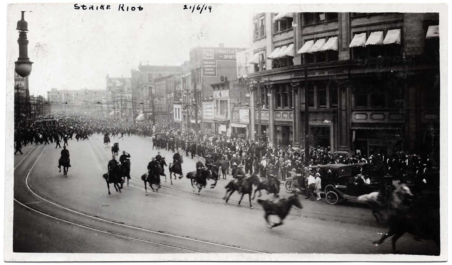 Police on horses charge around the corner of Portage Avenue and Main Street on Bloody Saturday. (William Wilson fonds/Archives of Manitoba)