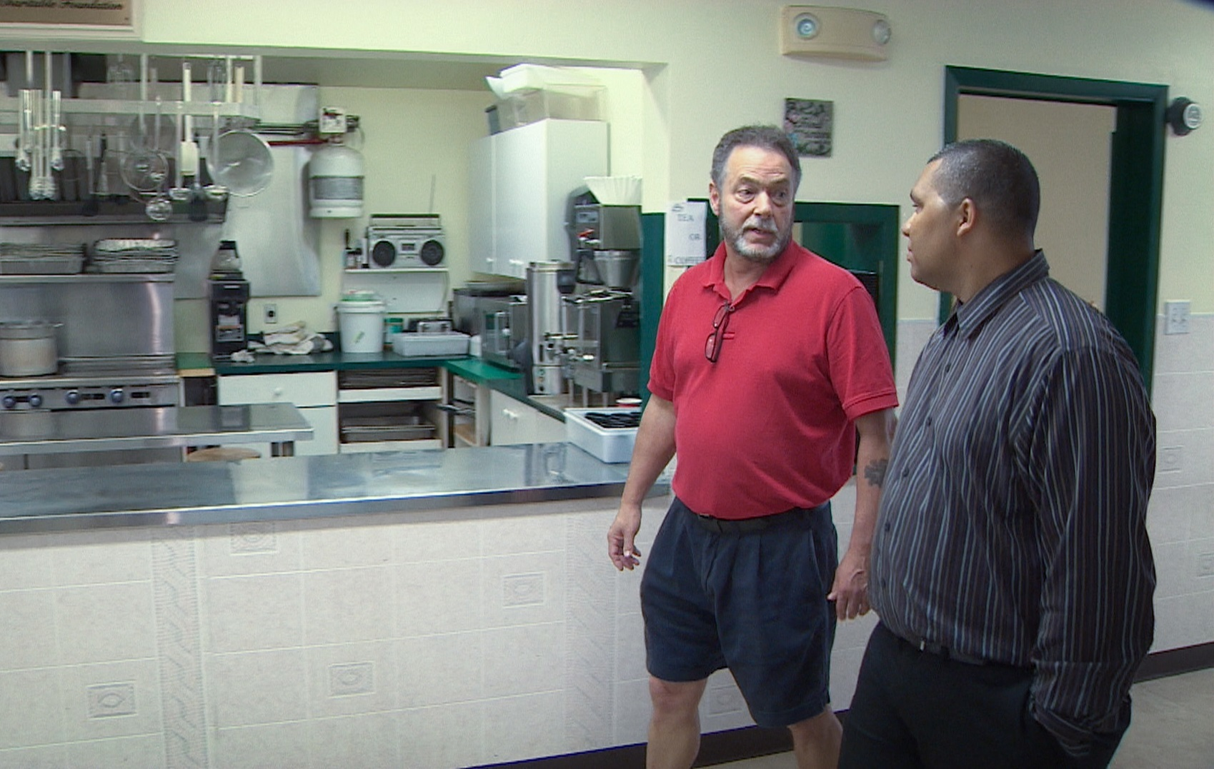 Hope Cottage executive director Joe Morgan, left, walks with Arsenault past the charity's kitchen. (Robert Short/CBC)