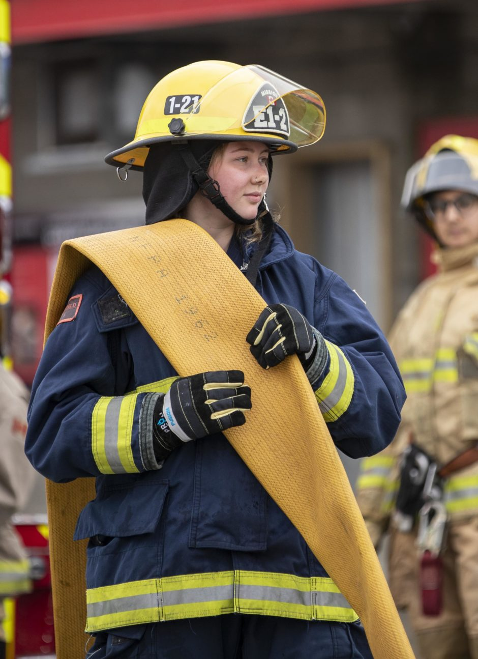 A teenage girl in firefighting gear holds a firehose.