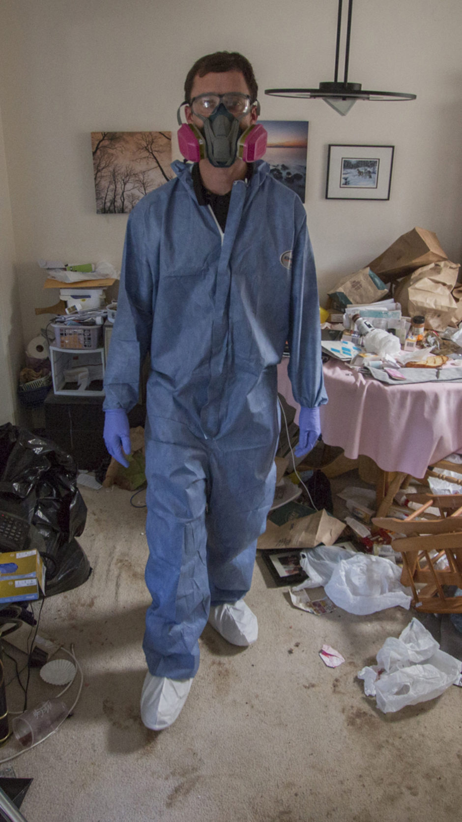 Curtis Kreklau, wearing protective gear, stands in the middle of a living room cluttered with garbage and debris.