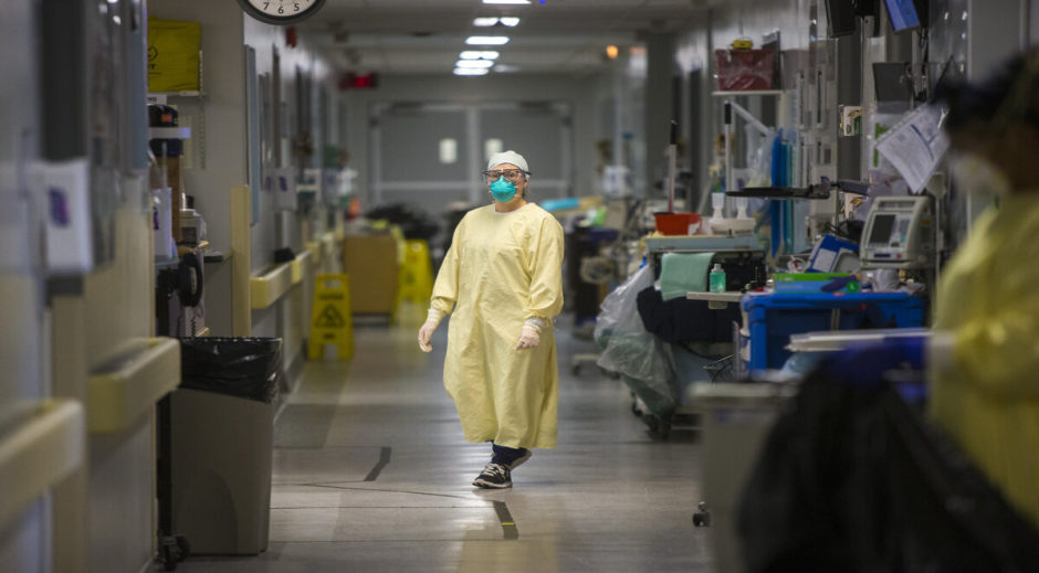 A health-care worker stands in a COVID positive unit.