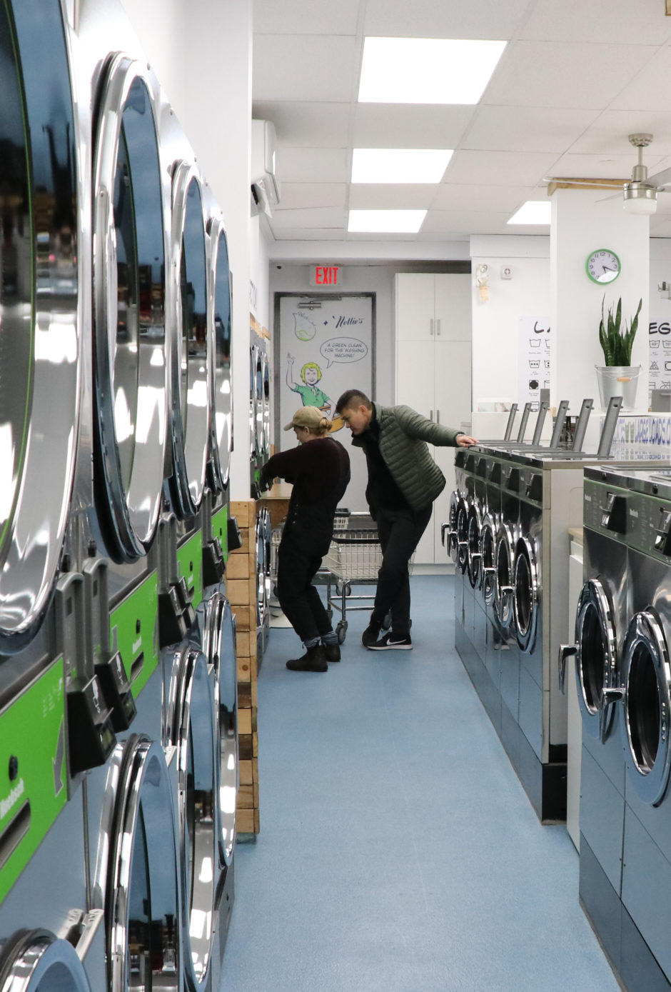 A staff member at a laundromat shows a customer how to use a dryer