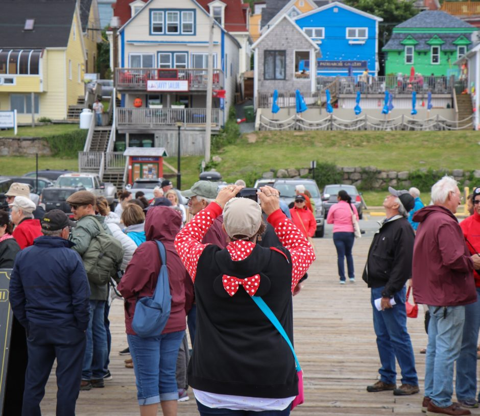 A tourist on a wharf in Lunenburg, N.S., snaps a photo of the historic town.
