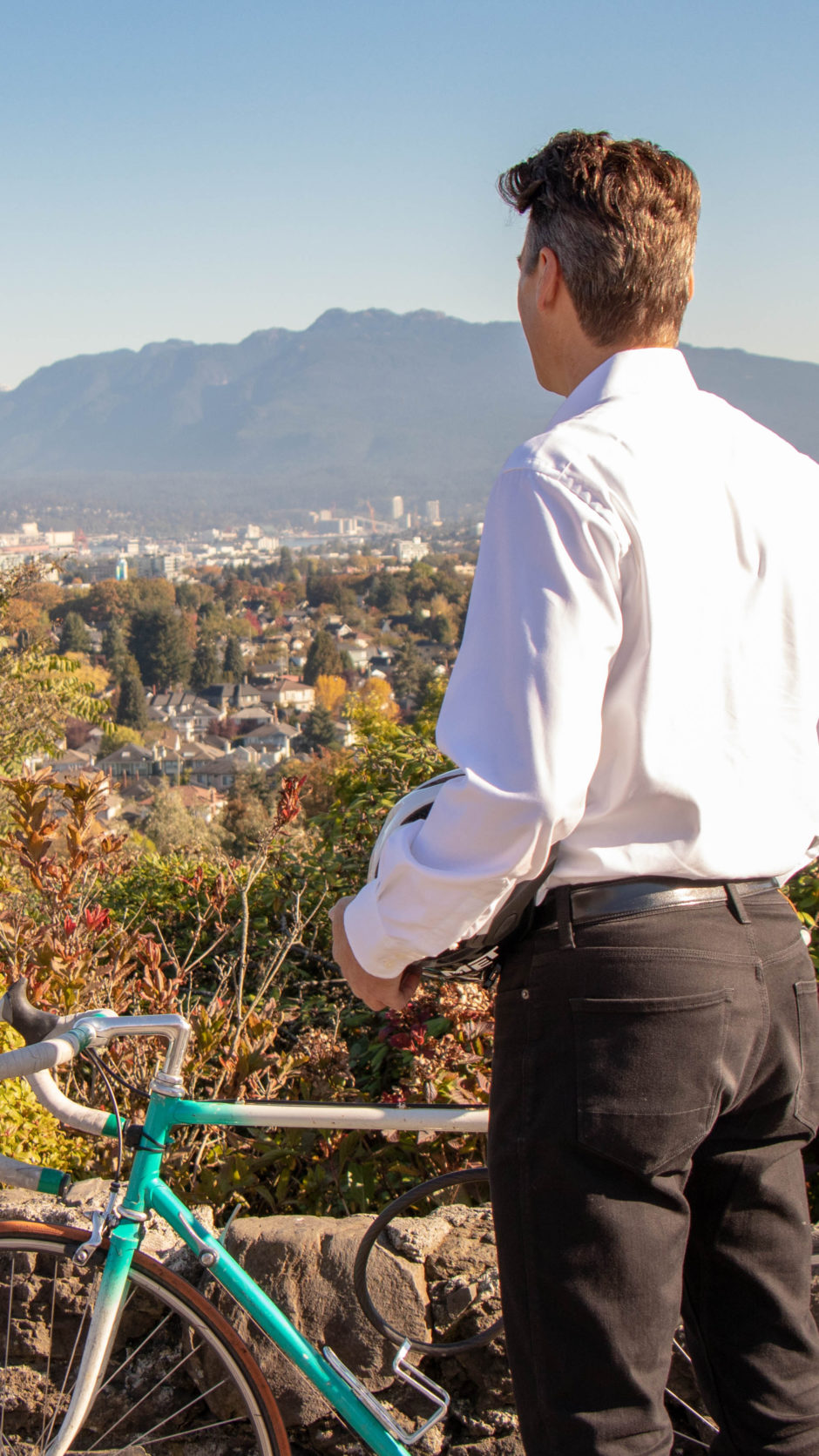 Gregor Robertson is looking at the skyline while standing next to a bicycle.