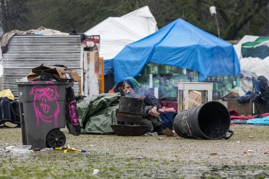 A woman sits by a small fire trying to keep warm in front of a collection of makeshift shelters and tents. (Ben Nelms)