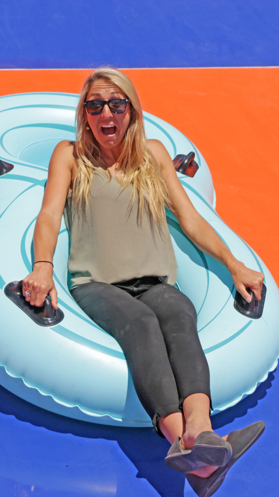 Waterslide designer Emily Colombo sits on a raft on a waterslide.