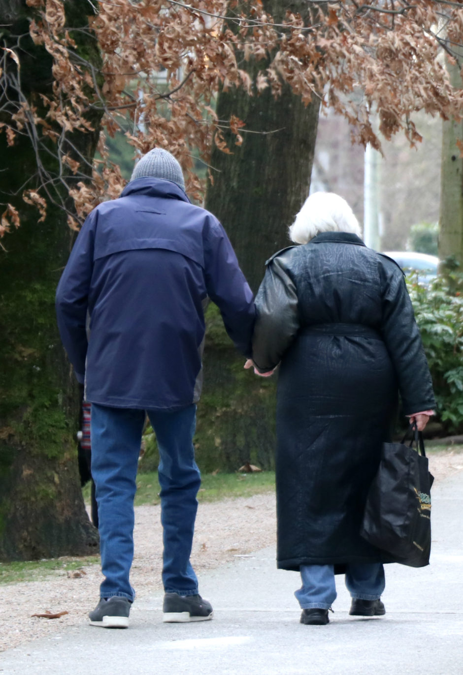 An older couple walks down a tree-lined street in Vancouver