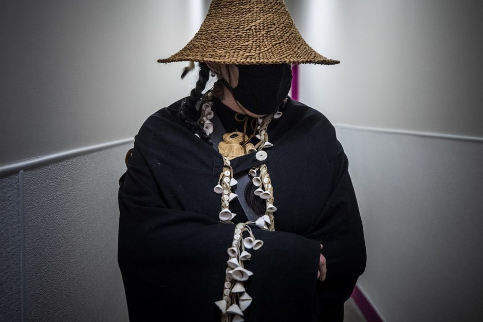 A woman stands draped in a traditional Haida shawl and woven basket hat with her face hidden behind a black mask.