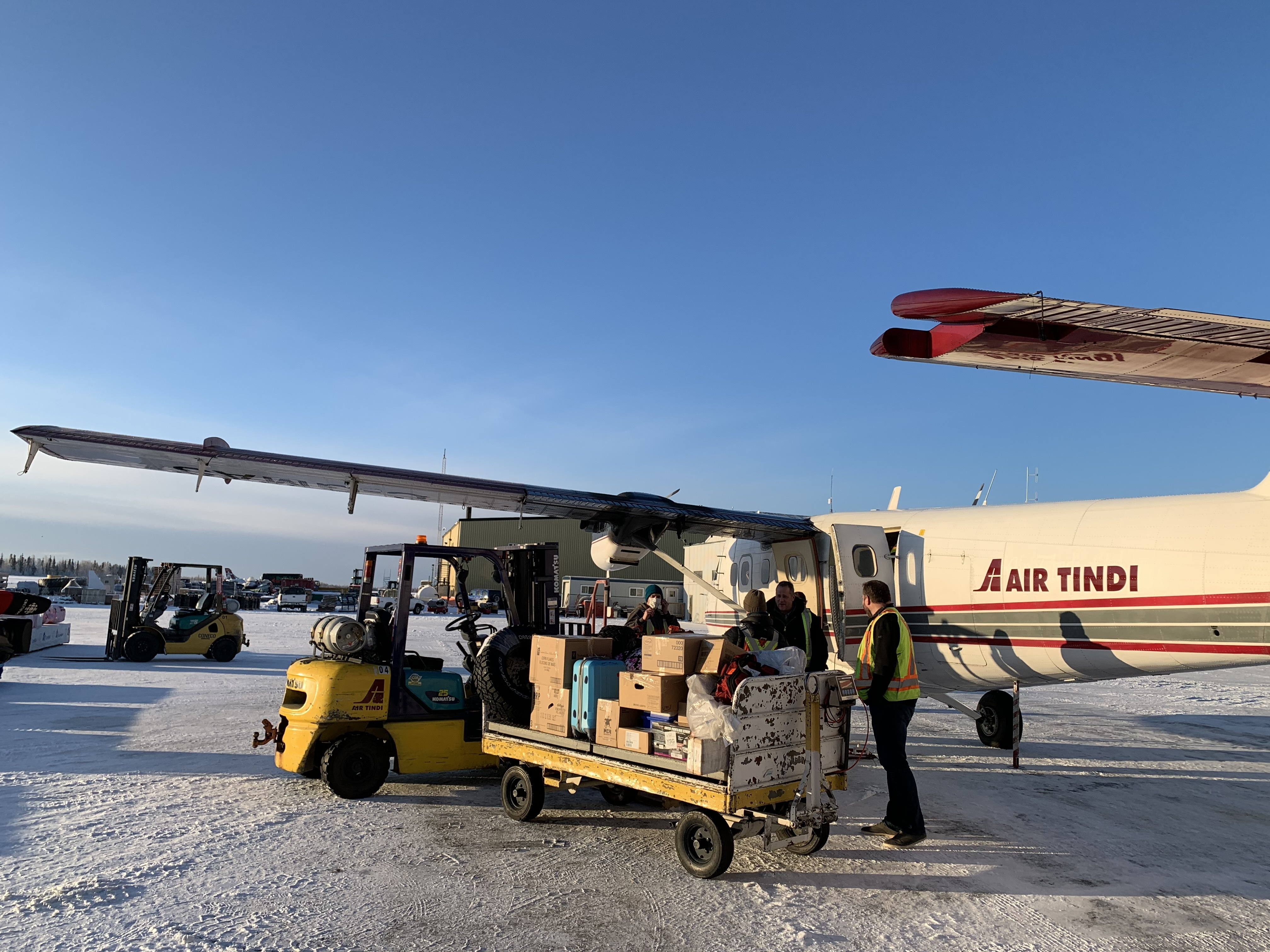 Air Tindi workers load a plane with cargo, which at times has included vehicle parts, building materials, or even livestock. (Sidney Cohen/CBC)