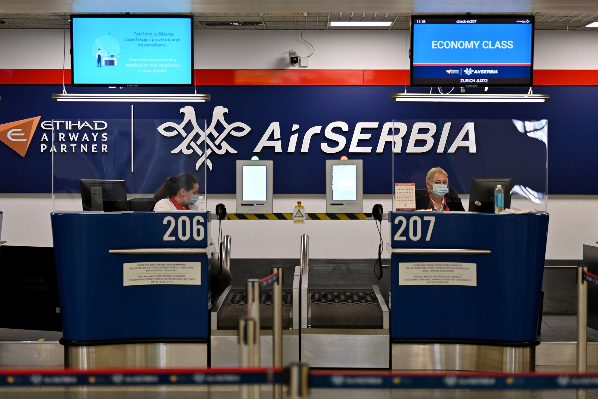 Airport personnel wait for passengers behind Plexiglas at the check-in counters at Belgrade's airport. (Andrej Isakovic/AFP via Getty Images)