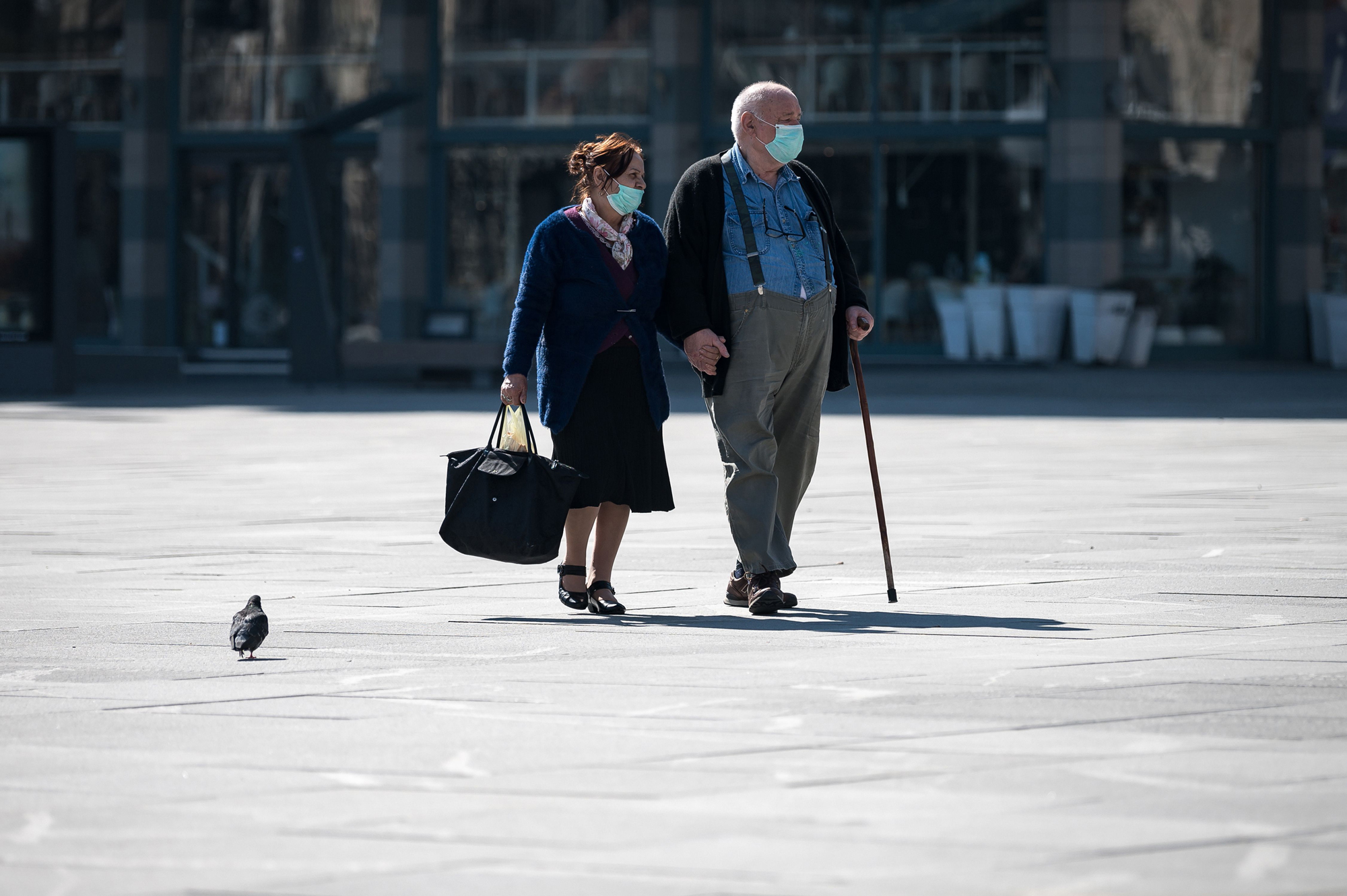 An elderly couple wearing protective masks walks through Belgrade's main square on March 17, after Serbia's president said the new restrictions were necessary to 'save our elderly.' (Andrej Isakovic/AFP via Getty Images)