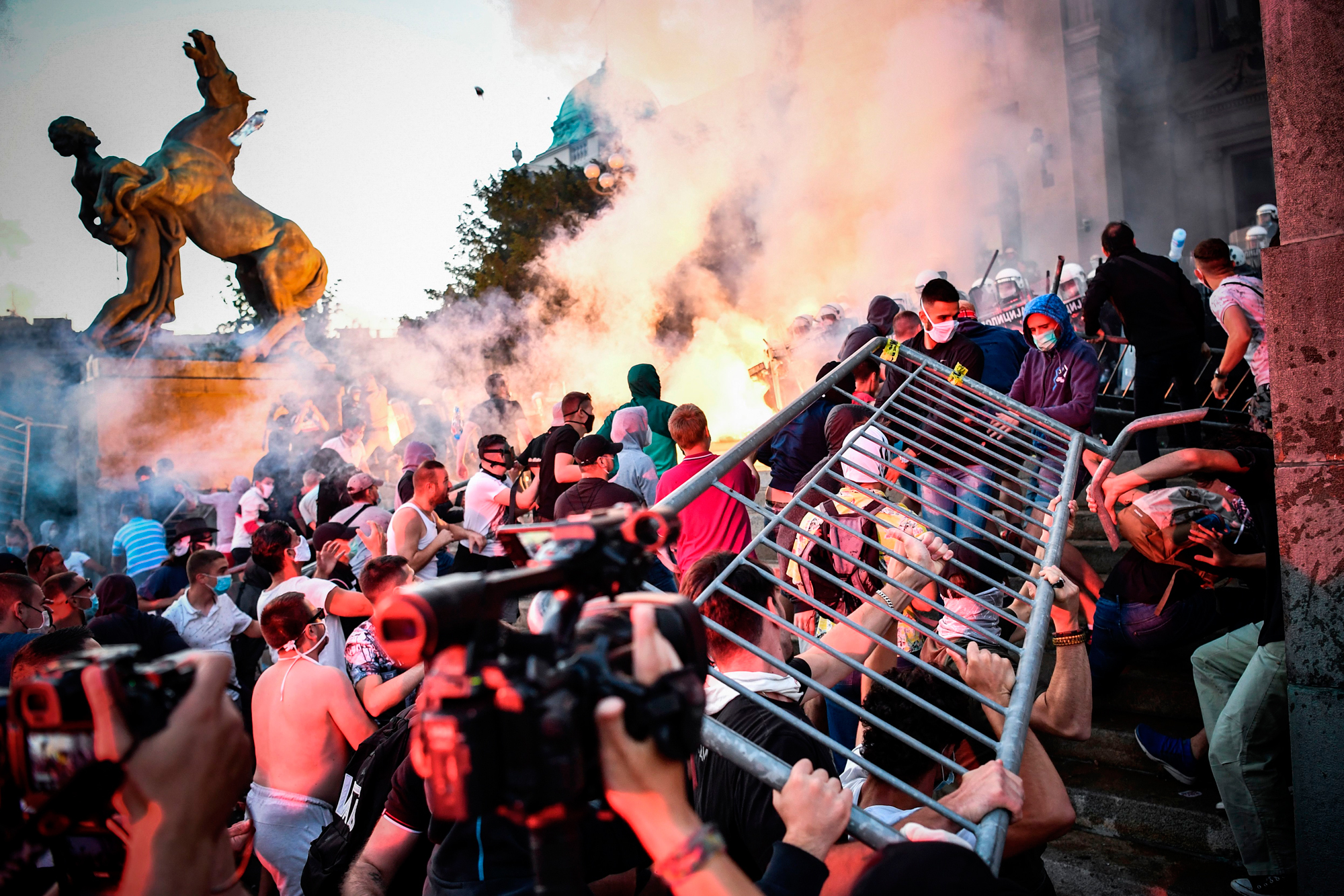 Protesters clash with police in front of Serbia's National Assembly building in Belgrade on July 8 during a demonstration against a weekend curfew announced to combat a resurgence of COVID-19 infections. (Andrej Isakovic/AFP via Getty Images)