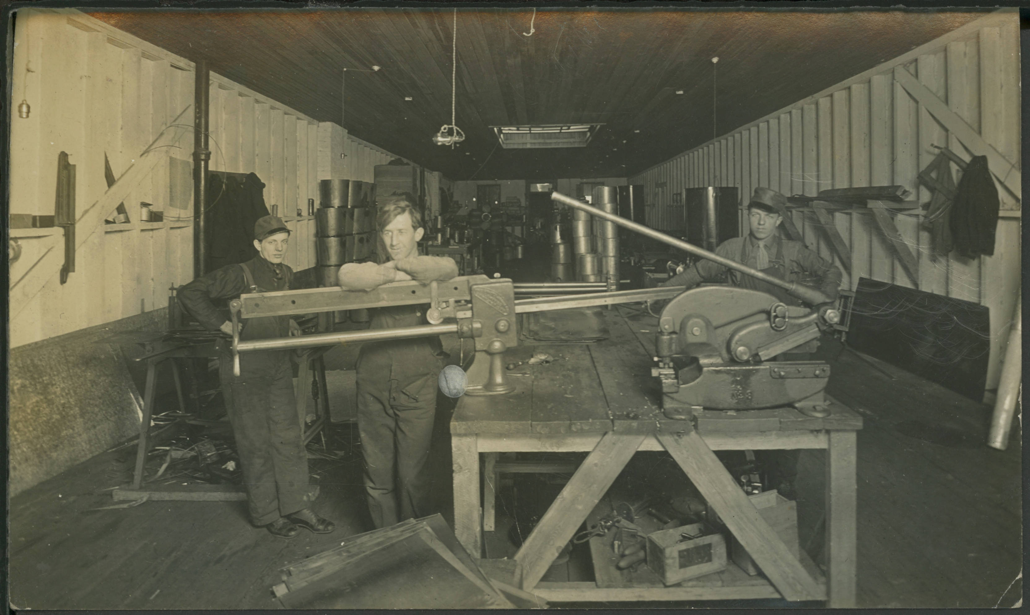 Three men stand in a railway shop in this Winnipeg postcard from 1911. (Martin Berman Collection/Winnipeg Public Library)