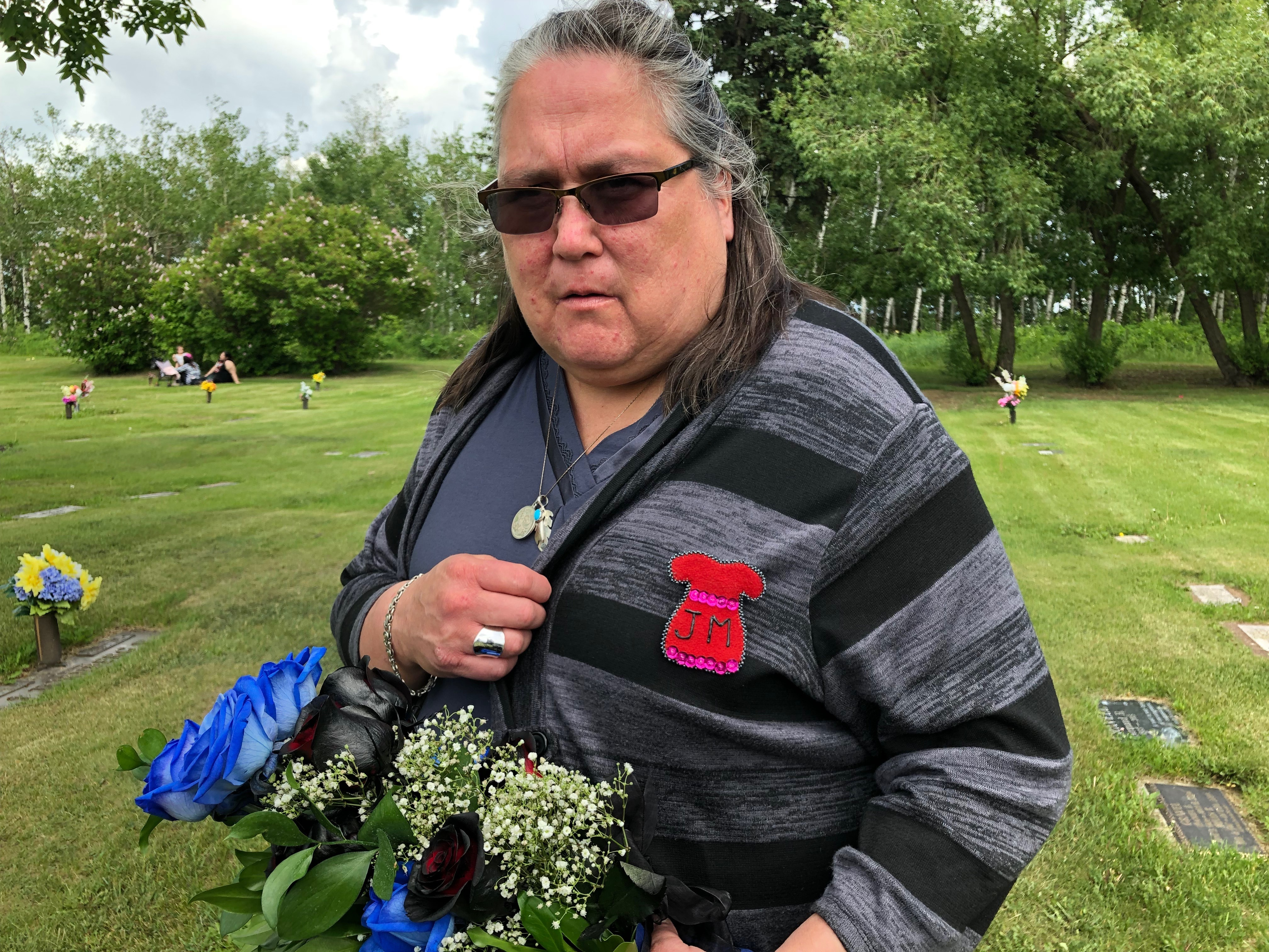 Betty Bird at the Edmonton graveyard where her friend is buried. Bird is wearing a red dress pin, a symbol for missing and murdered Indigenous women, with Mercredi's initials. (Rachel Zelniker/CBC)