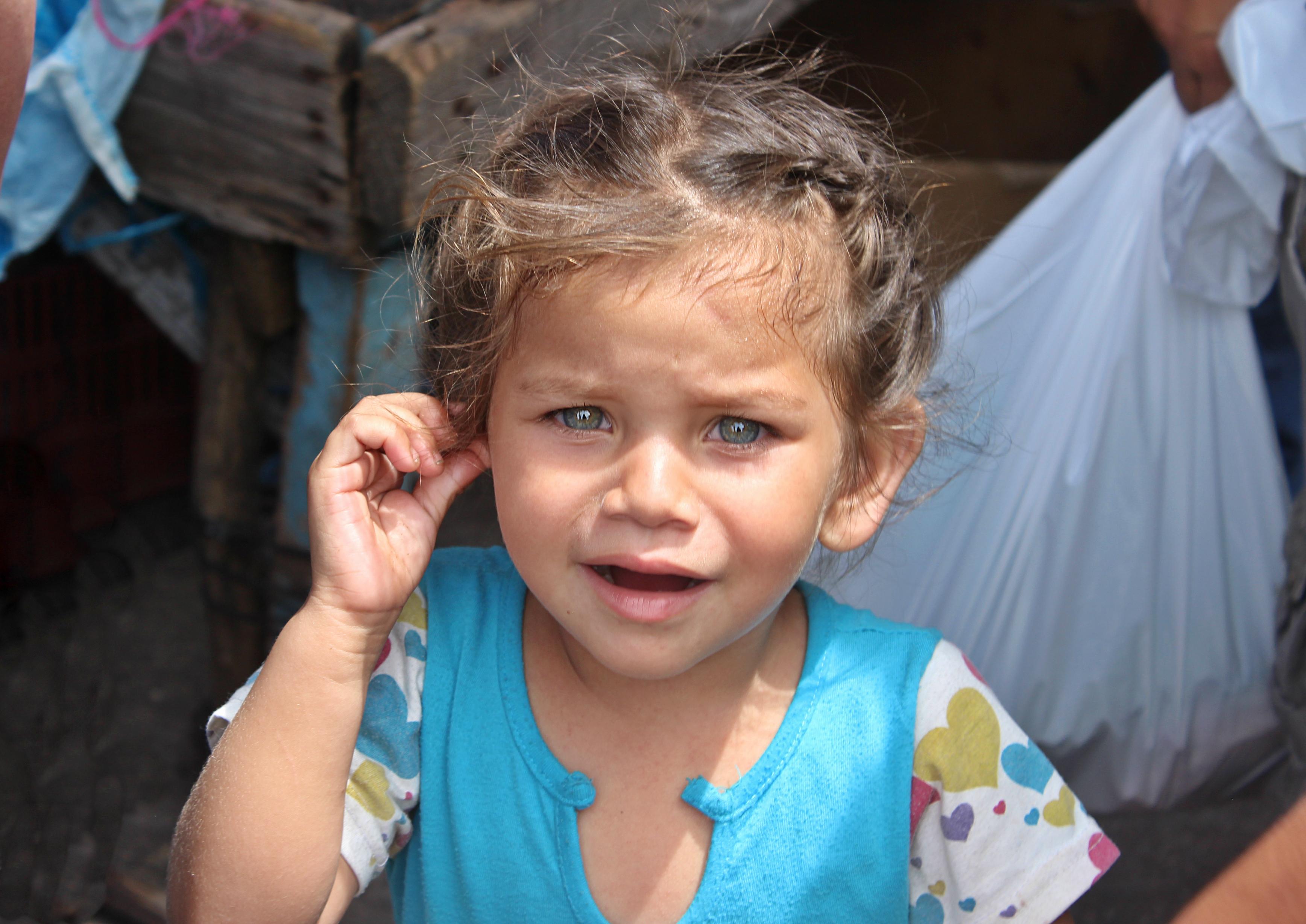 Four-year-old Génesis Naomi Sierra cries while walking through El Mayoreo, Tegucigalpa's farmers market, with her mother. (María José Burgos/CBC)