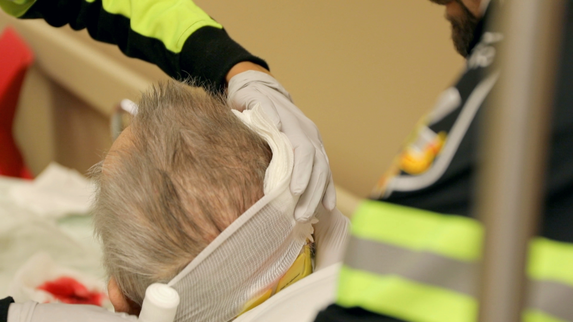 The emergency responders bandage the patient's head wound. (Paul Borkwood/CBC News)
