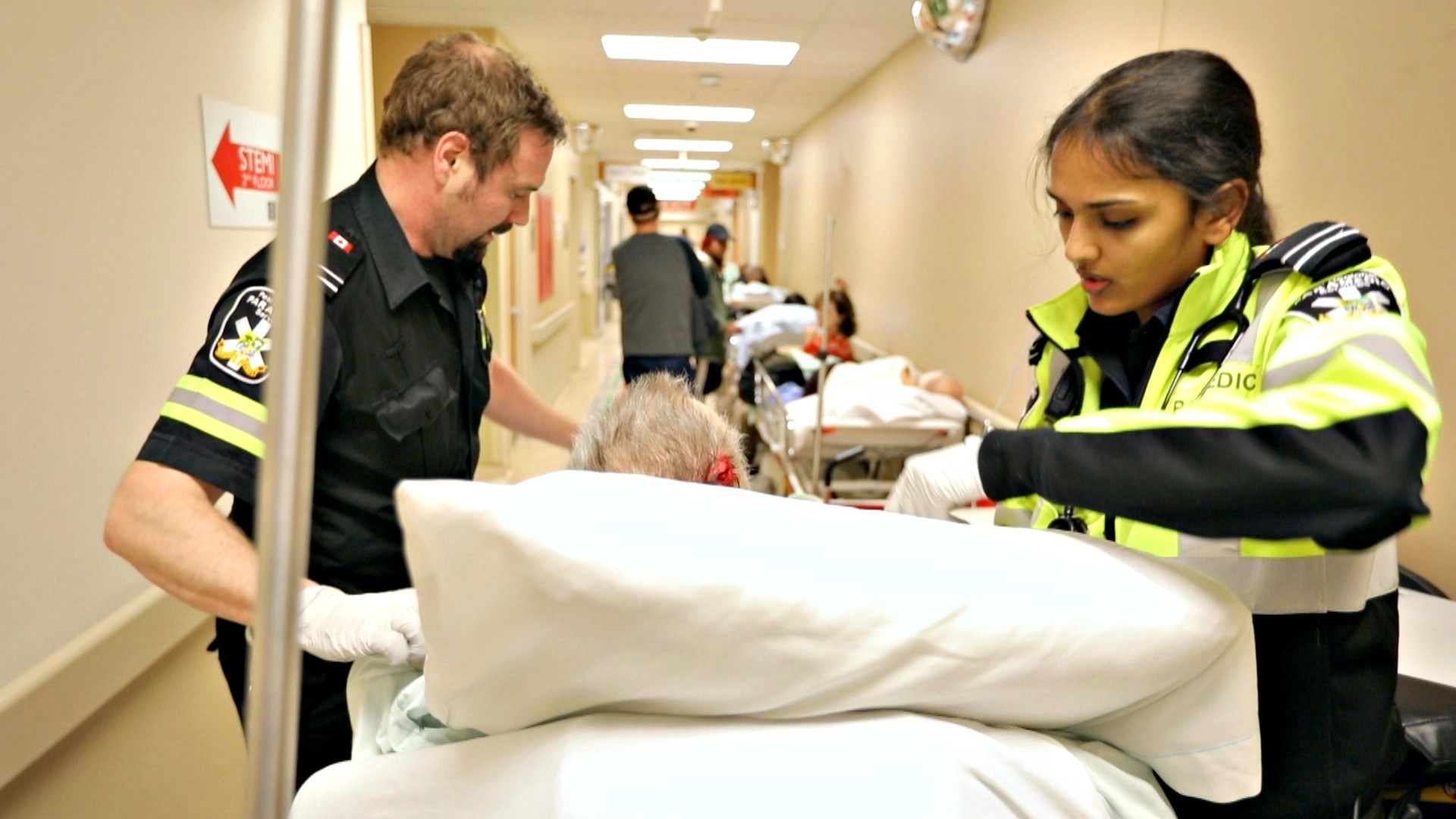Shortly before 7 p.m., paramedics bring another patient into the already-crowded hallway. (Paul Borkwood/CBC News)