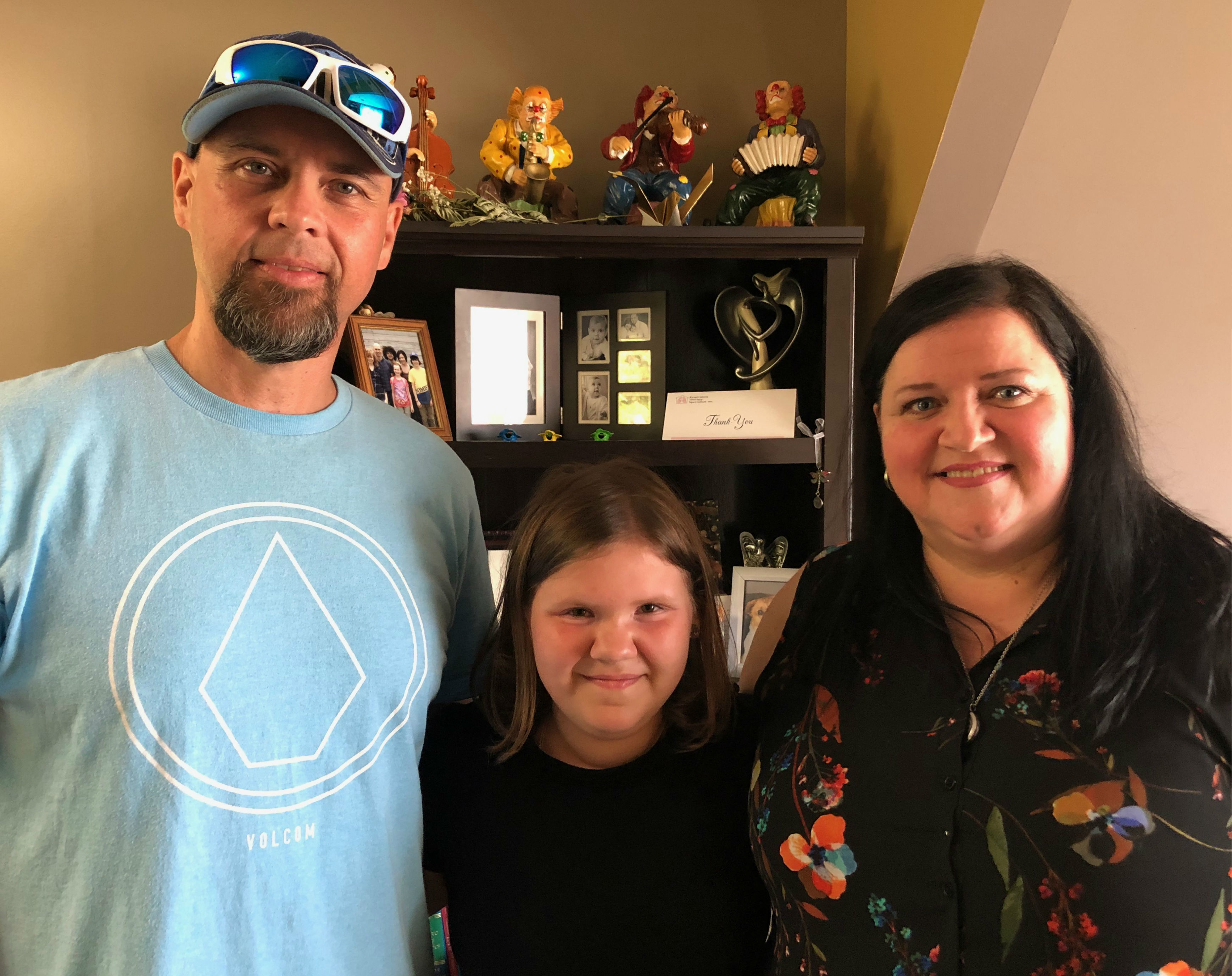 Brygette Park (centre) with her dad, Trevor Park (left), and her mom, Penny Lambert (right), at the family's home in Gillams. (Jen White/CBC)