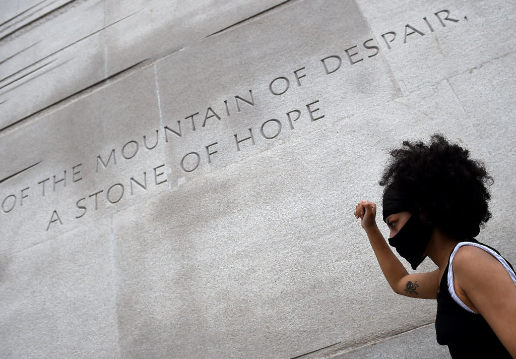 A woman walks past part of the Martin Luther King Jr. Memorial on the National Mall in D.C. during the Juneteenth protest. The memorial includes a massive statue of King inscribed on the side with a quote from his famous 1963 speech, I Have a Dream: 'Out of the mountain of despair, a stone of hope.' (Olivier Douliery/AFP/Getty Images)