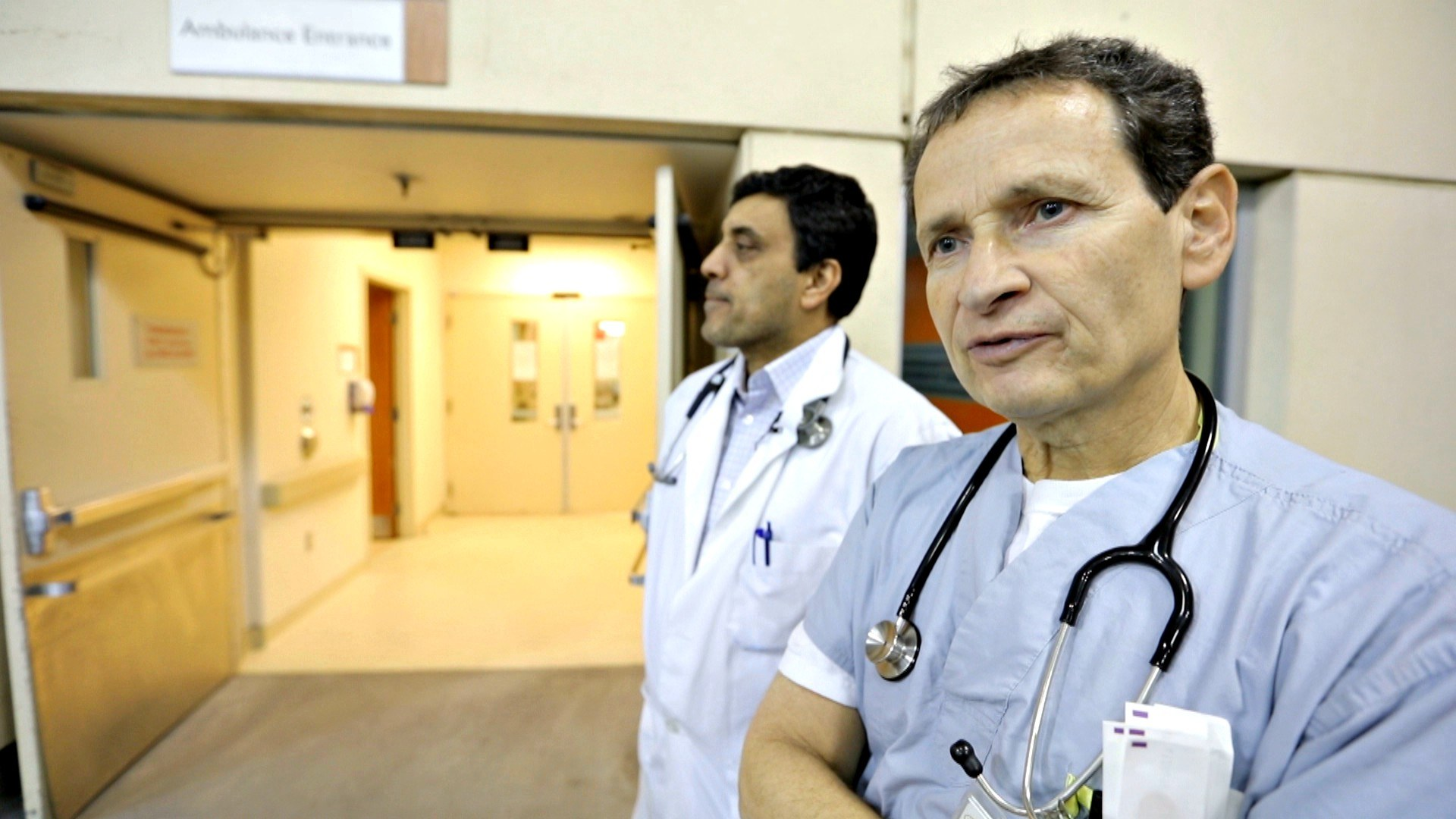 Dr. Naveed Mohammad and Dr. Oscar Karbi gaze out at the ambulance bay. (Paul Borkwood/CBC News)