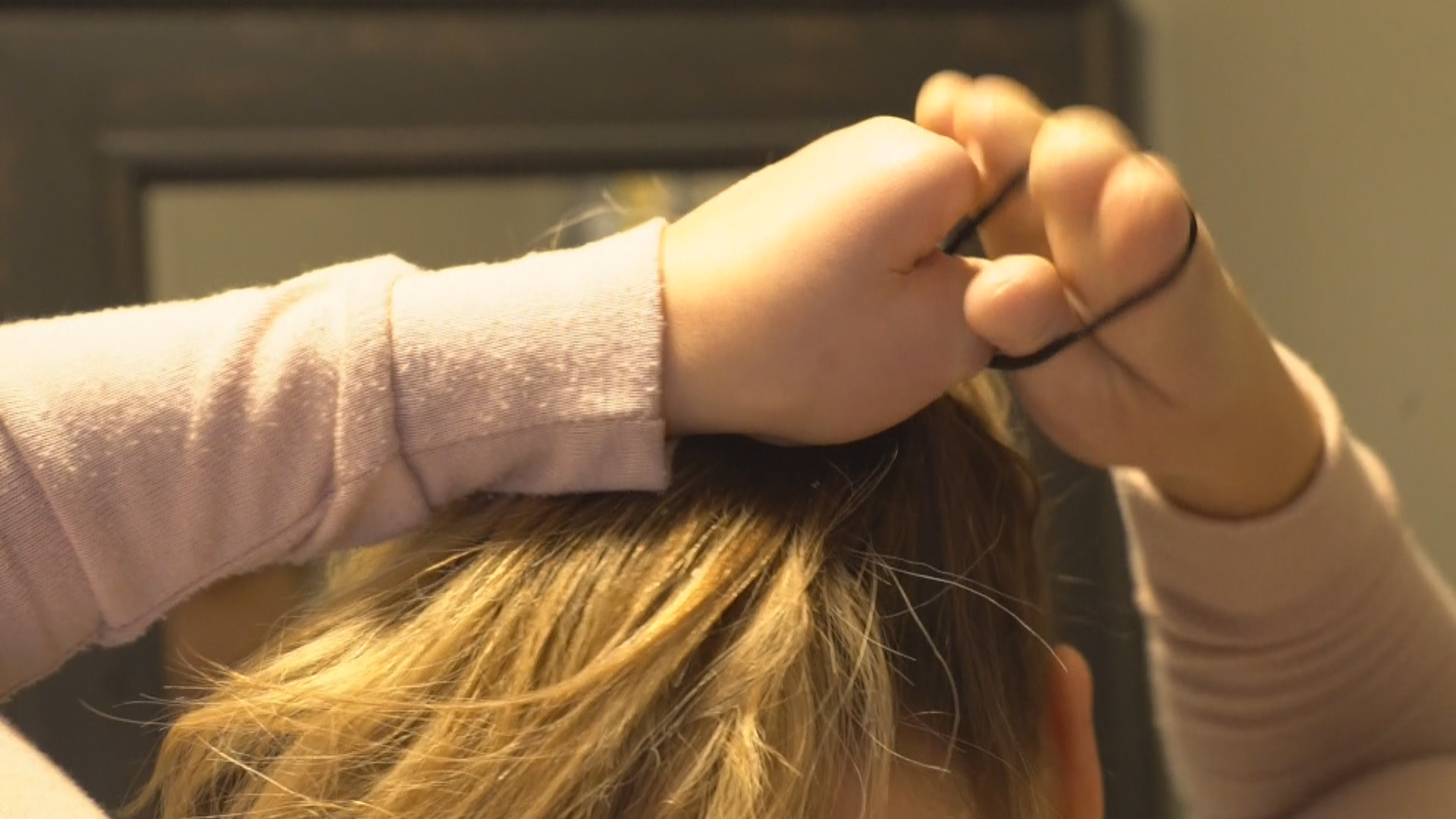 Elaine Dodge-Lynch demonstrates how she learned to put her hair up. (Gary Quigley/CBC)