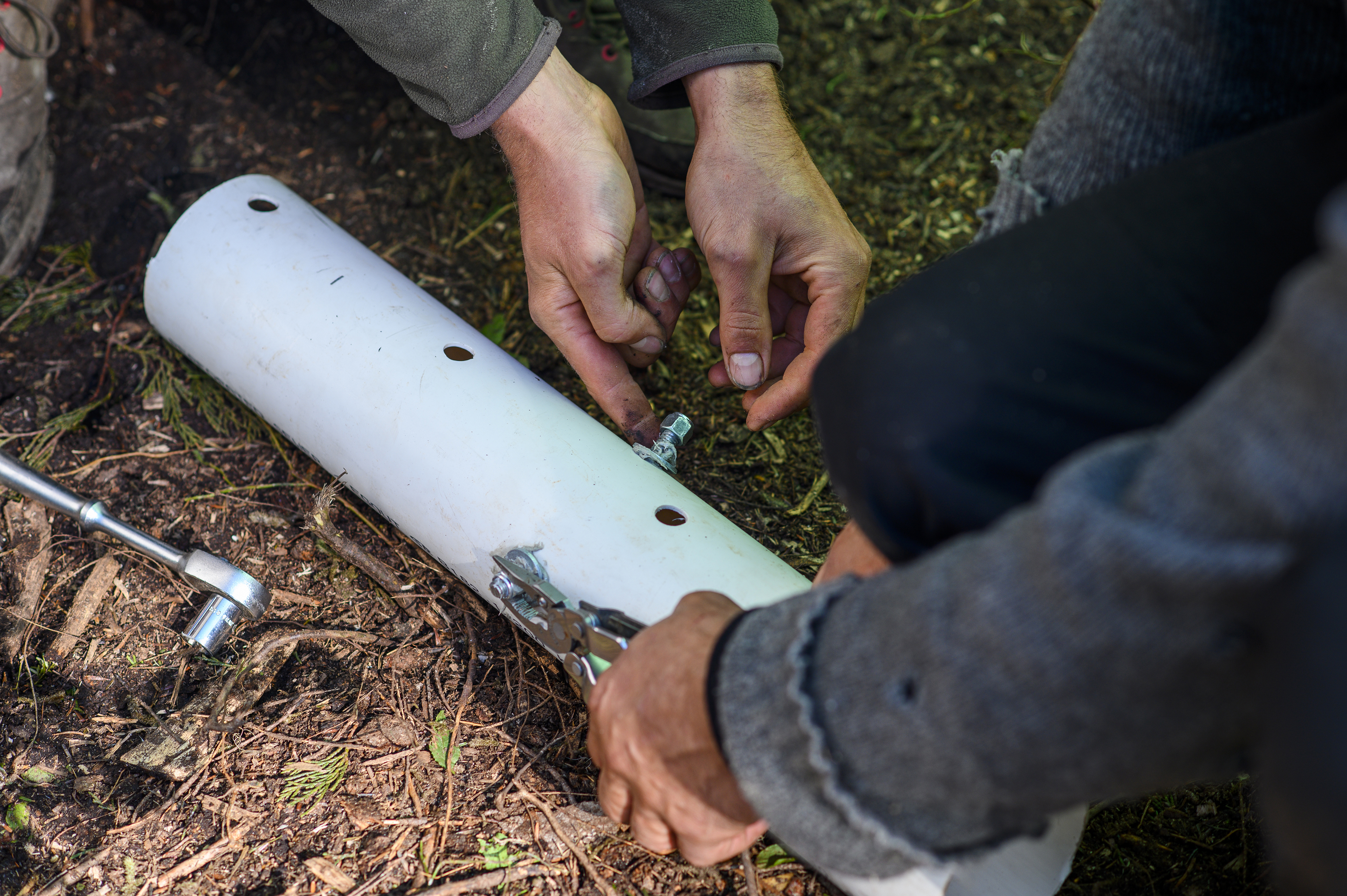 Activists use metal bars and glue to re-enforce PVC piping that will be cemented to the ground to thwart police and make it harder to remove the protesters from the camp. (Kieran Oudshoorn/CBC)