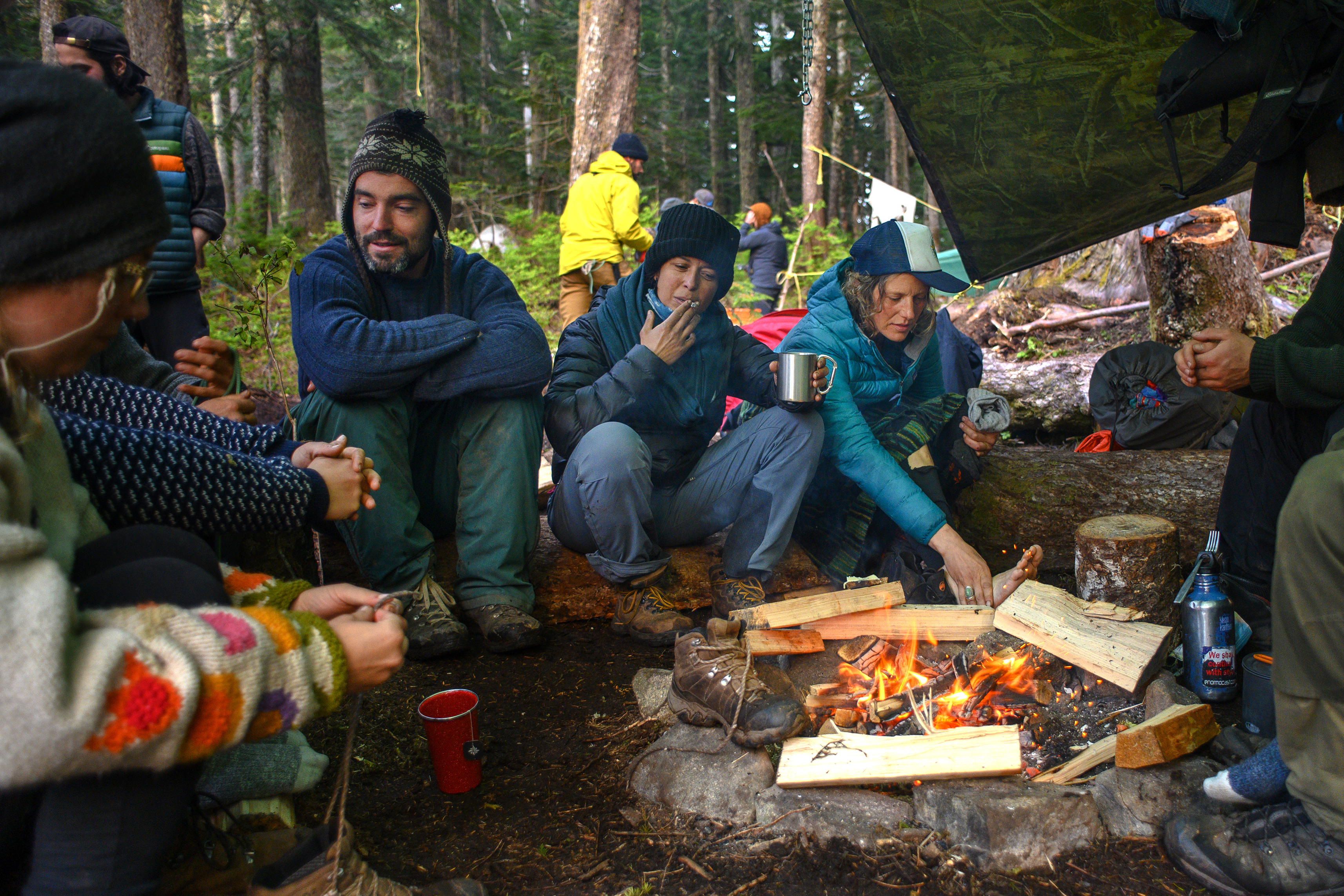 Activists at a protest site known as Ridge Camp near the headwaters of Fairy Creek on southwestern Vancouver Island rest and warm their feet by the fire. Some have been in the camp for months. (Kieran Oudshoorn/CBC)