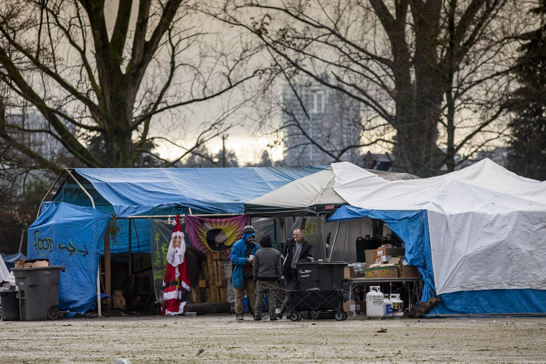 People gather around a makeshift kitchen at the park in December where donated food is available to campers. (Ben Nelms)