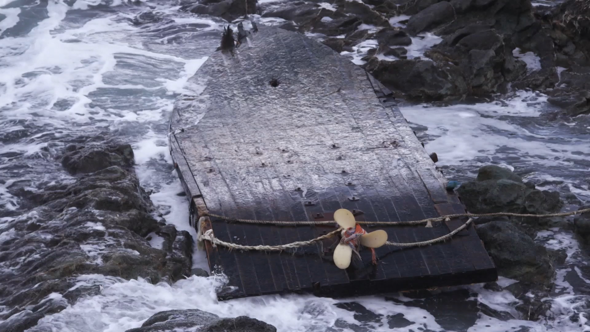 An overturned North Korean fishing boat washed up on the coast of Japan. North Korean fishermen seem to be venturing out into more dangerous waters as they get displaced by large Chinese trawlers fishing for squid in North Korean waters. (South Korea Fisheries Agency/The Outlaw Ocean Project)