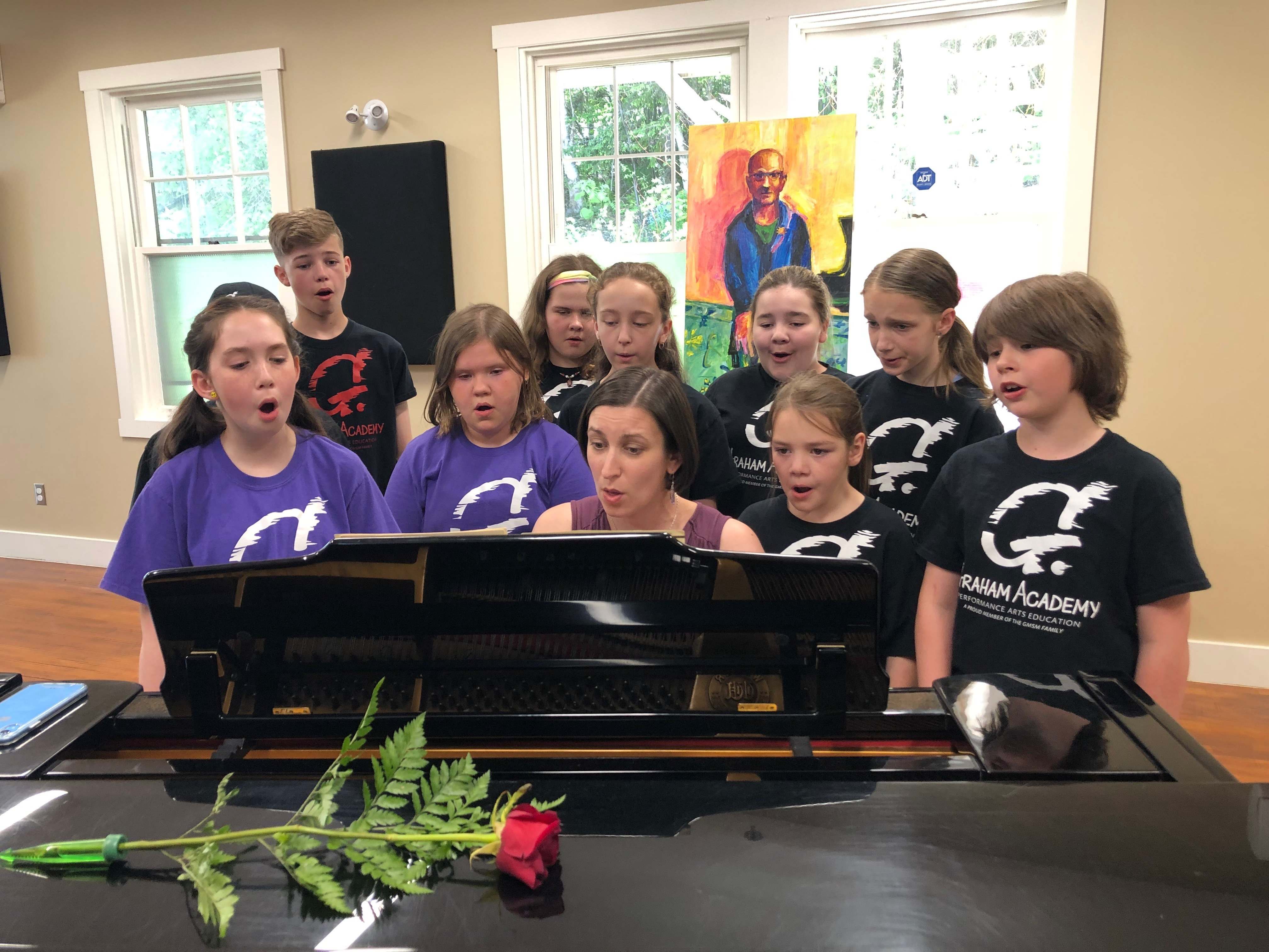 Students of the Graham Academy sing a song with choral instructor Jennifer Stratton-Renouf, as the memorial portrait of Gary Graham hangs in the background. (Jen White/CBC)