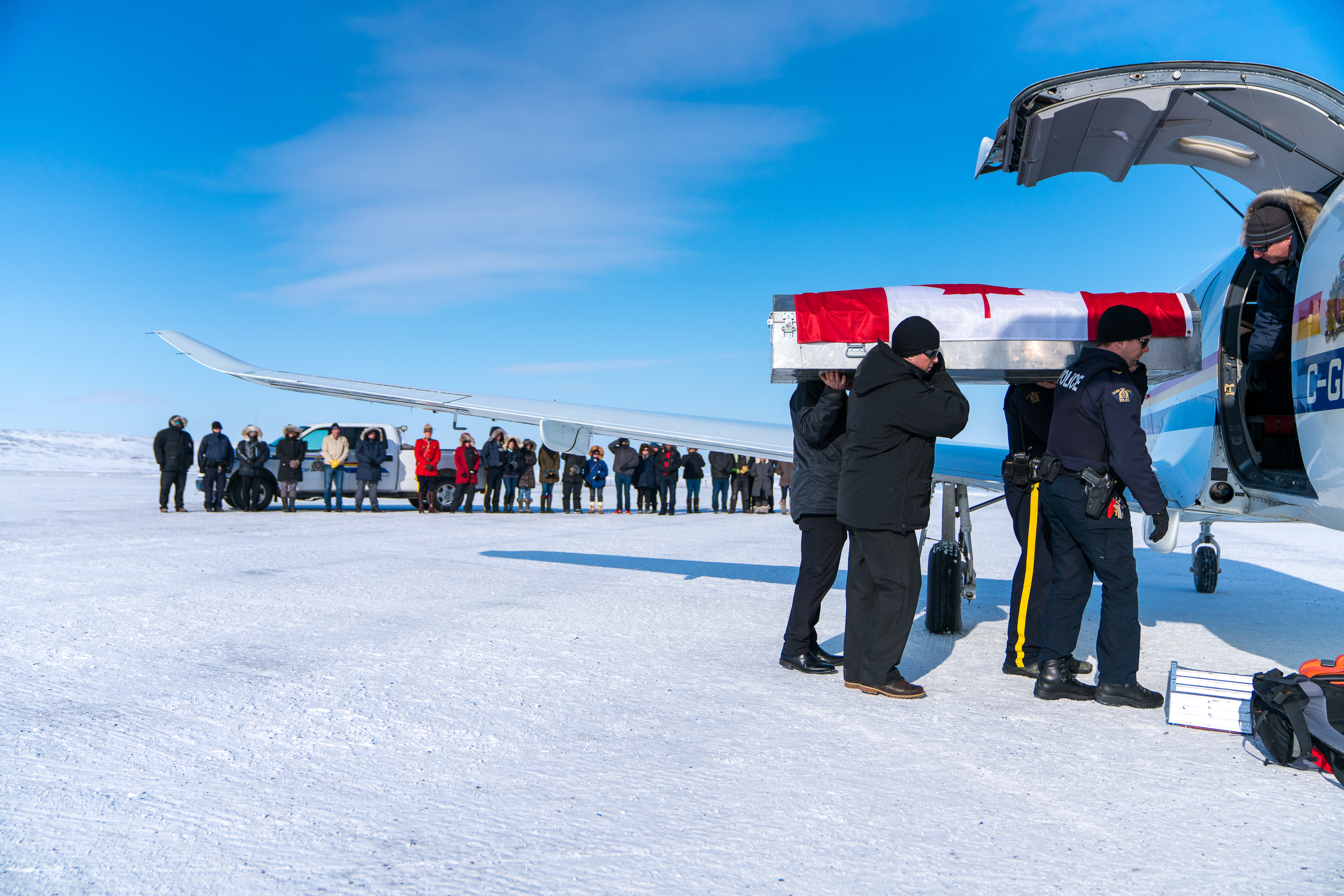 Community members watch as the body of Cst. Graham Holmes is loaded into an airplane in Kugluktuk, Nunavut. The 30-year-old died when his snowmobile went over a cliff in April 2018 (DnV Photo)