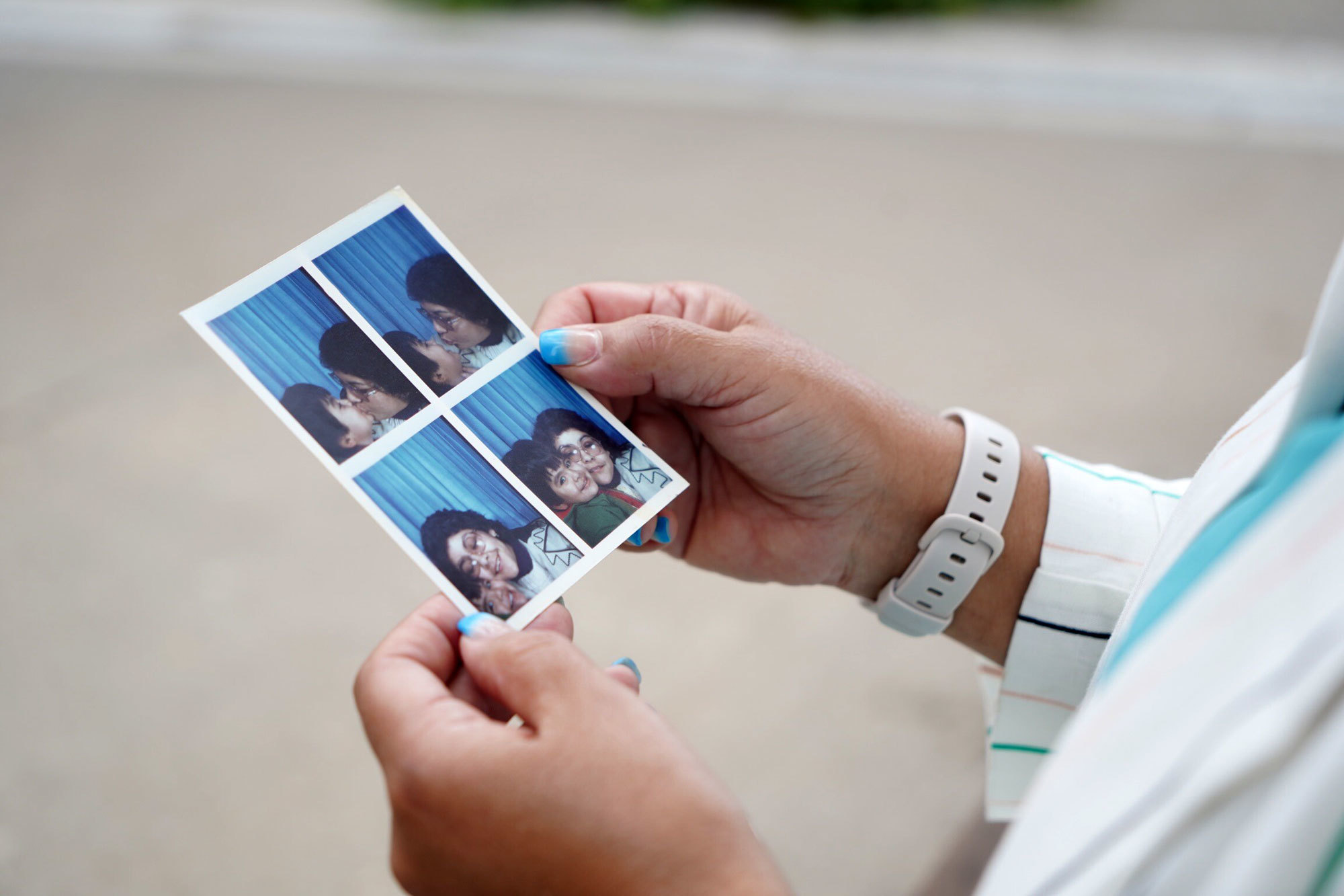 Jiménez holds photos of herself and her son taken shortly after they arrived in Canada at the end of 1983. (Charles Contant/CBC)
