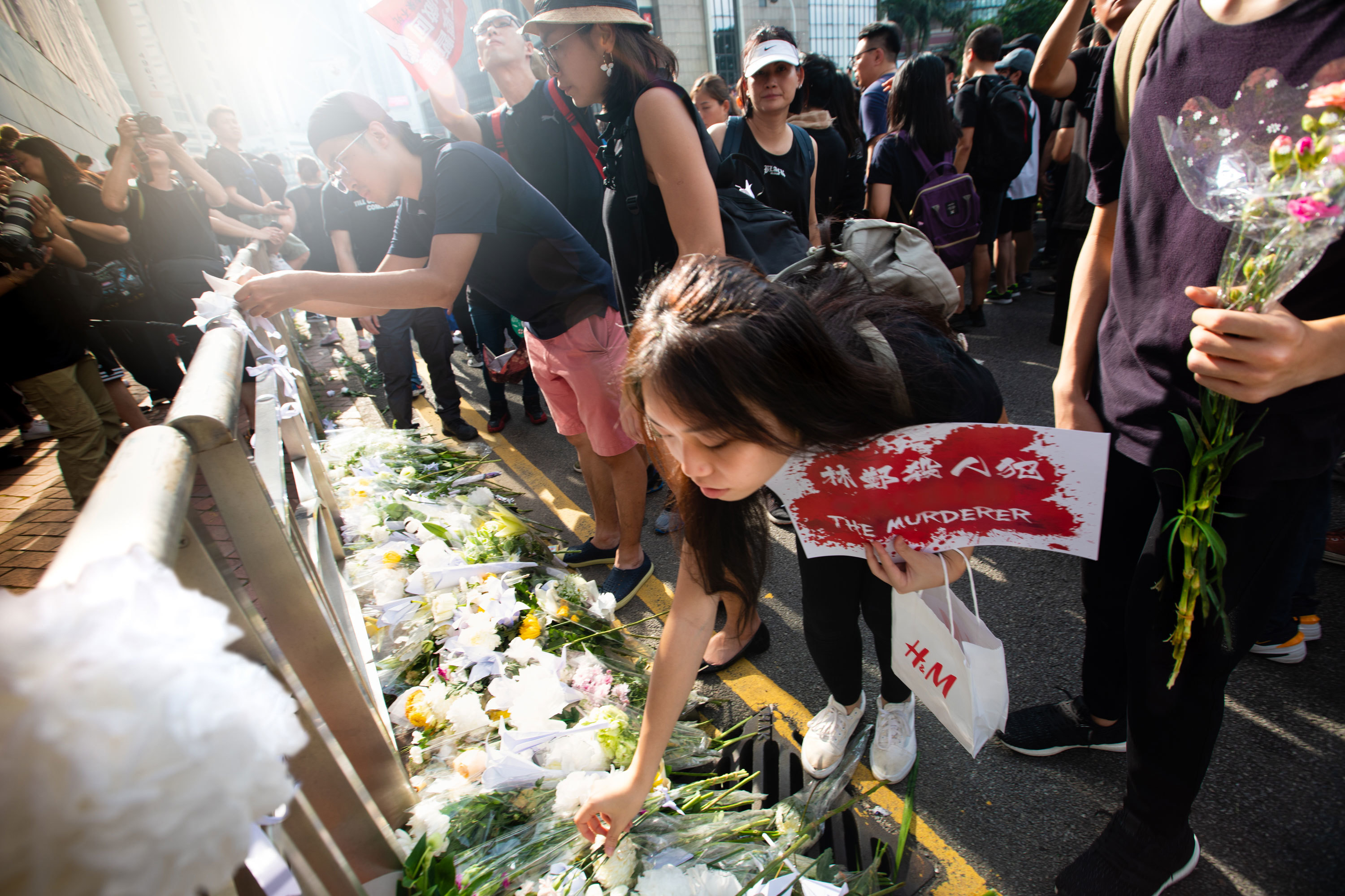 Mourners lay flowers at the memorial of a protester who took their own life. (Saša Petricic/CBC)