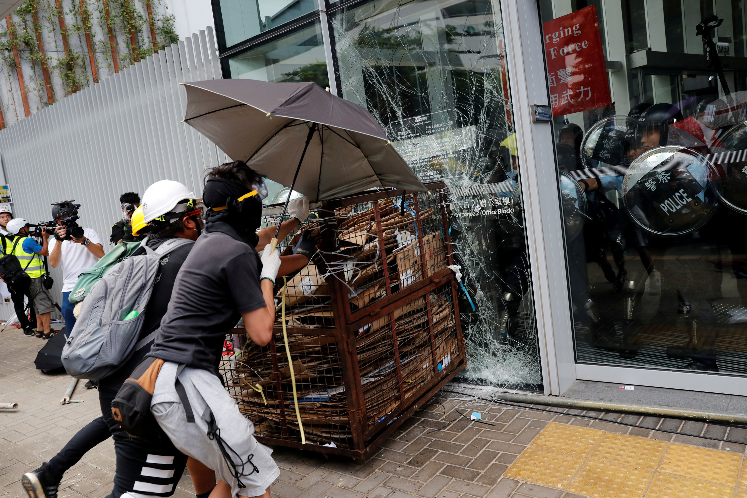 Protesters try to break into the Legislative Council building as riot police look on from inside. (Tyrone Siu/Reuters)