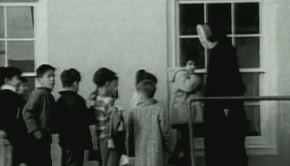 Indigenous children enter a residential school in this undated archival footage. (CBC Archives)