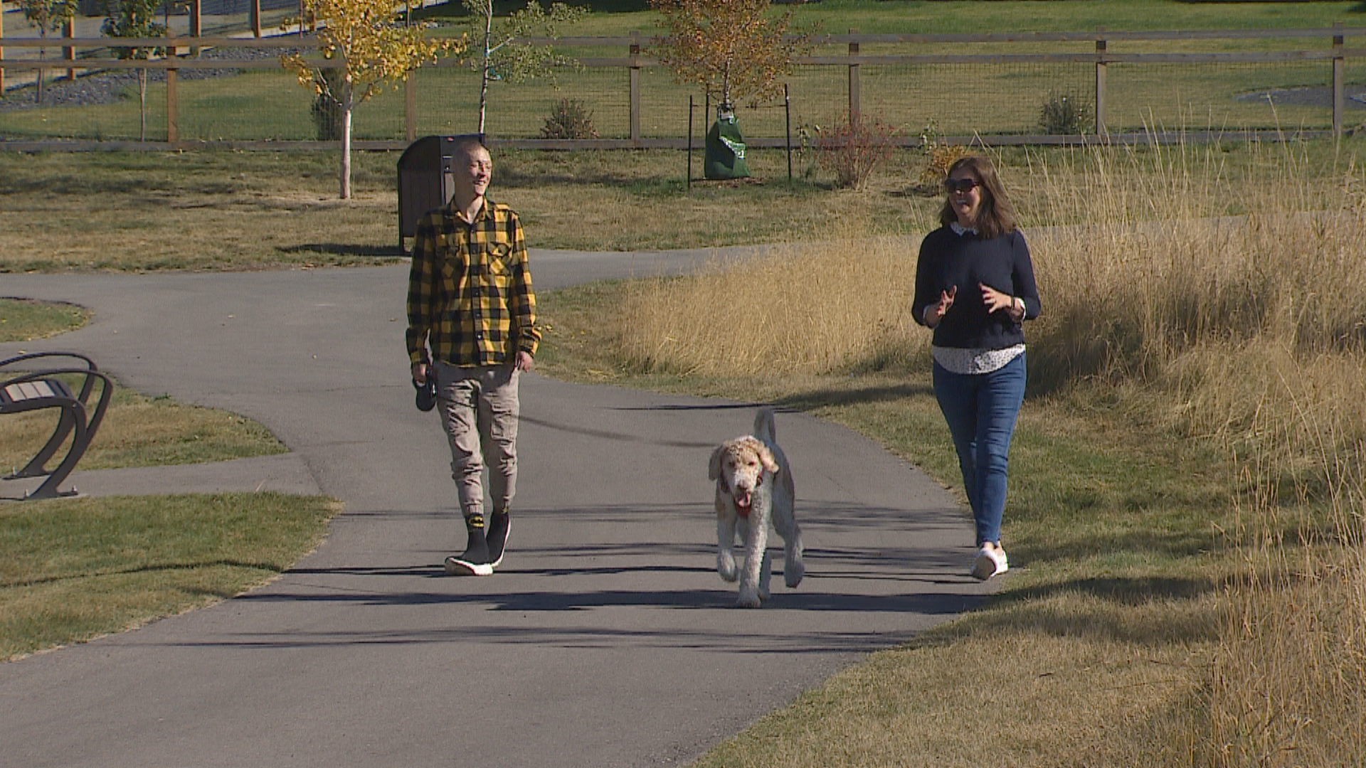 Kyle Hynes (left) walks with his dog, Simba, and his friend, Colette Williams (right), on a trail near his home in Springbank, Alta. (Justin Pennell/CBC)