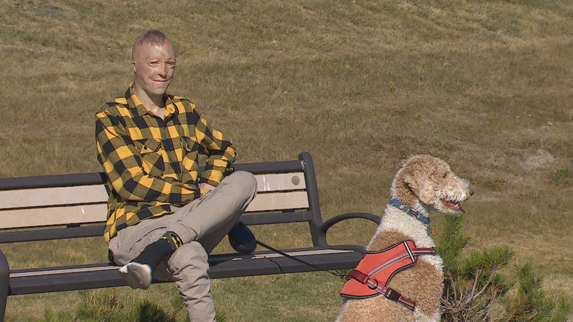 Kyle Hynes sits on a bench, taking a break from walking his dog Simba, on a trail near his home. (Justin Pennell/CBC)