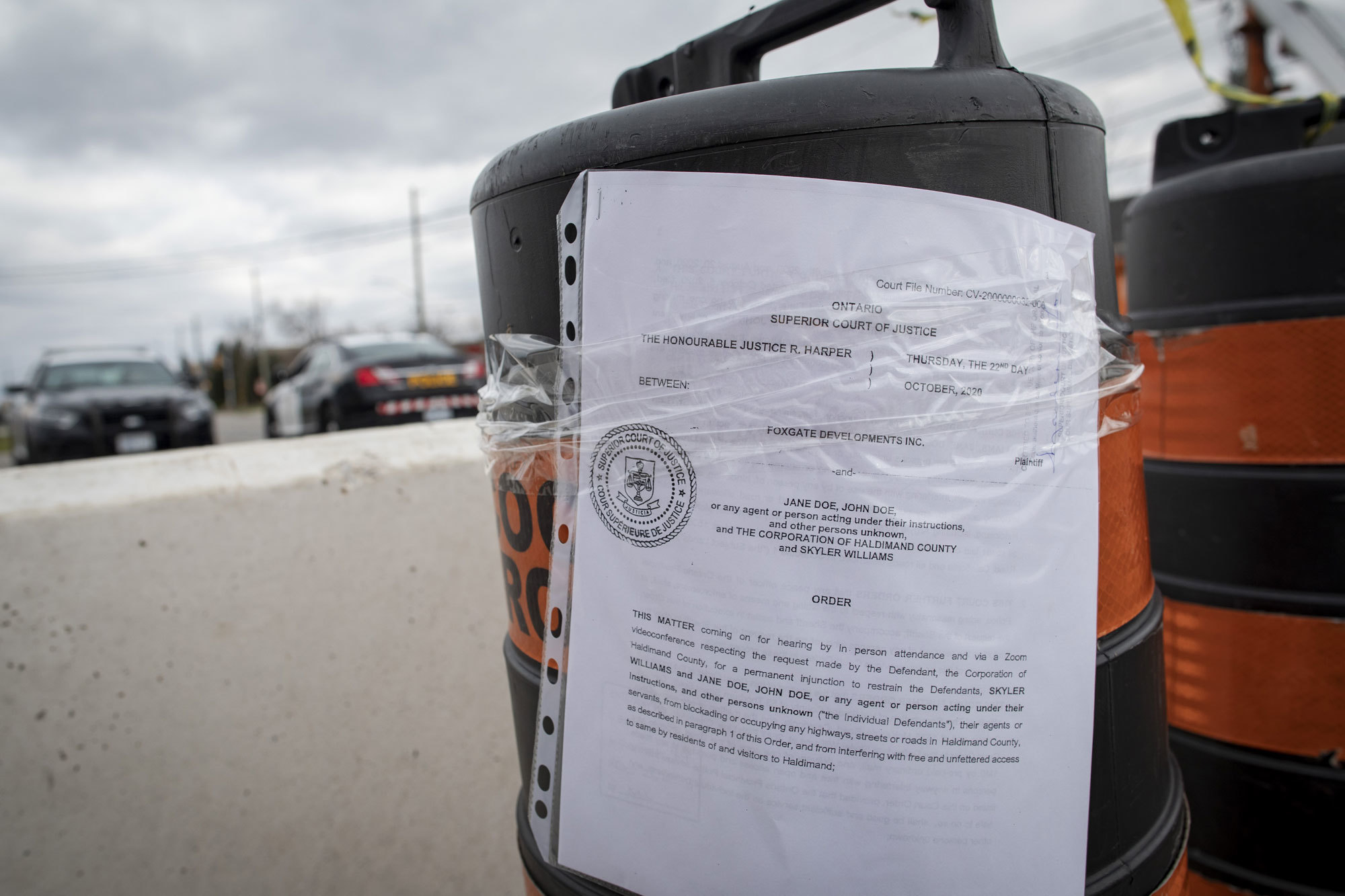 Top, a school bus acts as a barricade on Argyle Street South. Below, a copy of the injunction issued by Ontario Superior Court to halt the occupation of McKenzie Meadows is affixed to a pylon on Argyle. (Evan Mitsui/CBC)