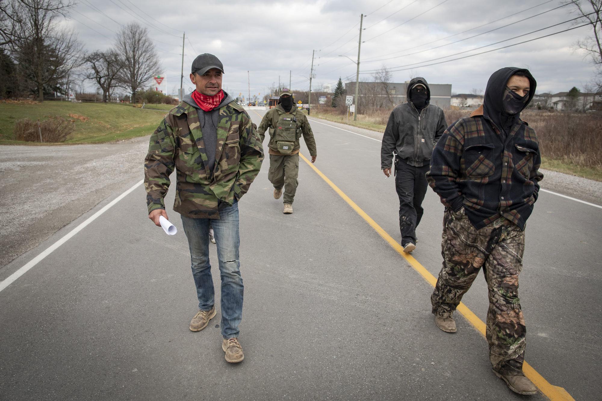 Skyler Williams, left, walks along Argyle Street South with fellow members of 1492 Land Back Lane. (Evan Mitsui/CBC)