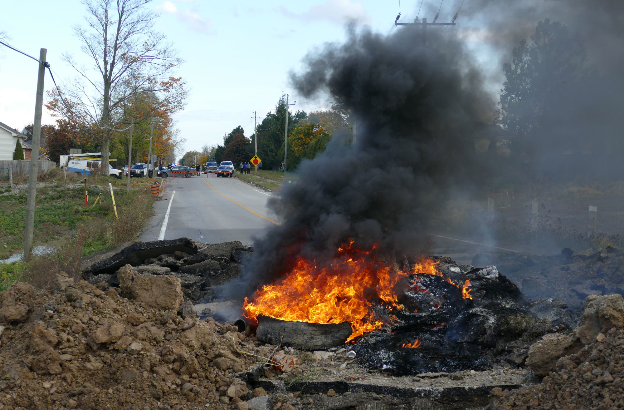 A tire fire set next to a trench dug in the road near the entrance to the McKenzie Meadows development, renamed 1492 Land Back Lane. (Jorge Barrera/CBC)