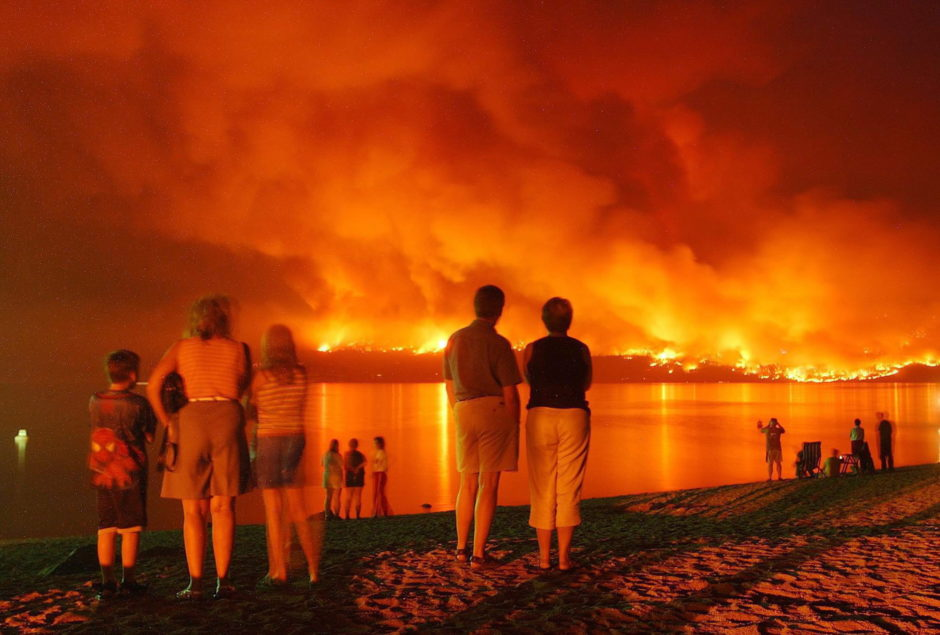 On Aug. 21, 2003, People gather at Marina Park near Kelowna, B.C. to watch flames across Lake Okanagan creeping closer to Mission area homes.