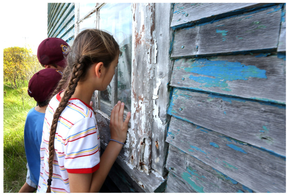 Left-Right: Beatrix Potter Elementary students Oscar Heard, Sasha Cellino and Sophia Anderson look through the window of the abandoned home of Silas Edgecombe in Ochre Pit Cove. Photo by Paul Daly for CBC