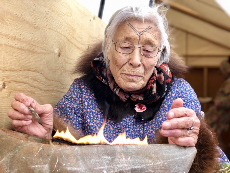 Bessie Pihoak Omilgoetok lights a qulliq — a traditional Inuit stone lamp. It's a skill that was passed on to her from her grandmother, and now she's hoping to pass it on to the next generation of Inuit. (Kate Kyle/CBC)