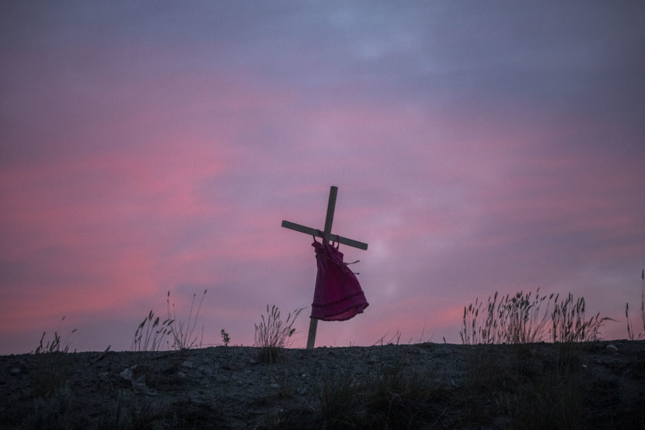 The silhouette of a red dress is seen on the hillside before sunset in Kamloops, B.C.