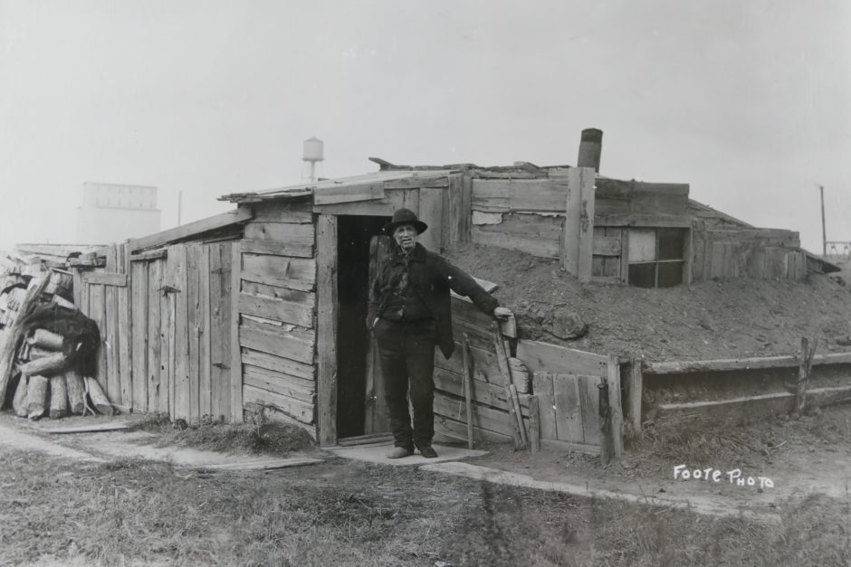 An old man stands outside a shack made of dirt and wood in the slums of Winnipeg between 1906 and 1910. (Foote collection/Archives of Manitoba)