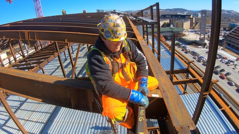 A steelworker fixes a metal beam into place at Memorial University's Core Science Facility. (CBC)