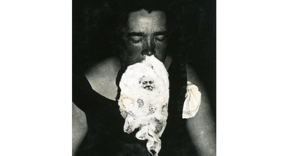 Medium Mary Marshall sits in a seance at T.G. Hamilton's home, with ectoplasmic excretions on her face.