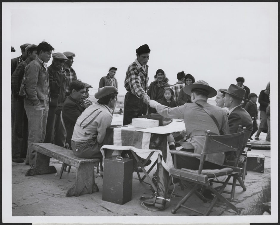 A Dene man accepts money from a fully uniformed Mountie seated behind a table draped with a British flag.